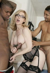 Nina Hartley cupping black scrotum.