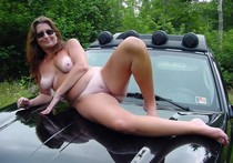 Naughty wife and loving mom posing naked outdoors on engine cowling of her car... great..