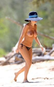 Lara Bingle caught topless on the beach
